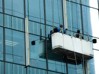Workers crane cradle clean windows glass of high building under sun day light blur sky, Hoist washer cleaning platform elevator maintenance on skyscraper high-rise tower facade, copy space text logo